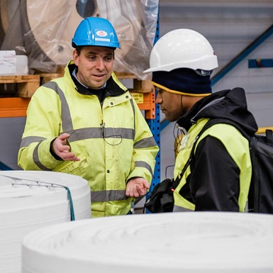 2 workers with hardhats talking in a facility