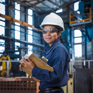A worker smiles while holding a clipboard in a manufacturing facility