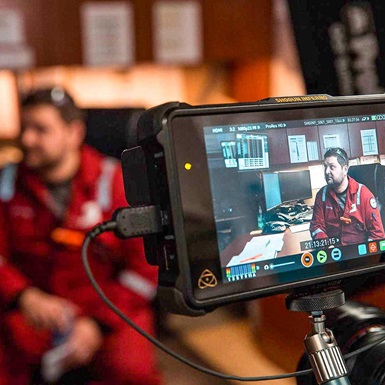 Detail shot from behind the scenes of Jeremy interviewing BP company man aboard Parker Drilling rig 272