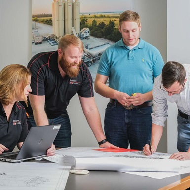 A group of young employees examine blueprints
