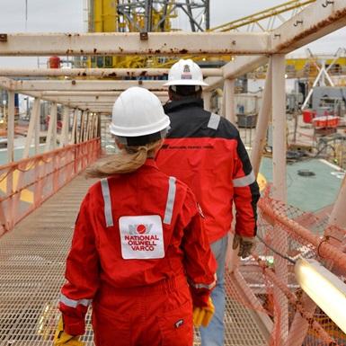 A trainee follows a mentor toward a rig