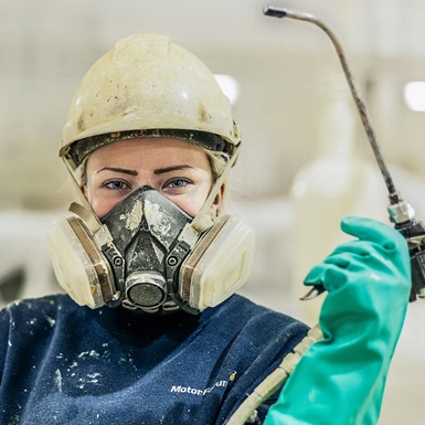 A young NOV employee smiles with a spray painting nozzle while wearing safety equipment.