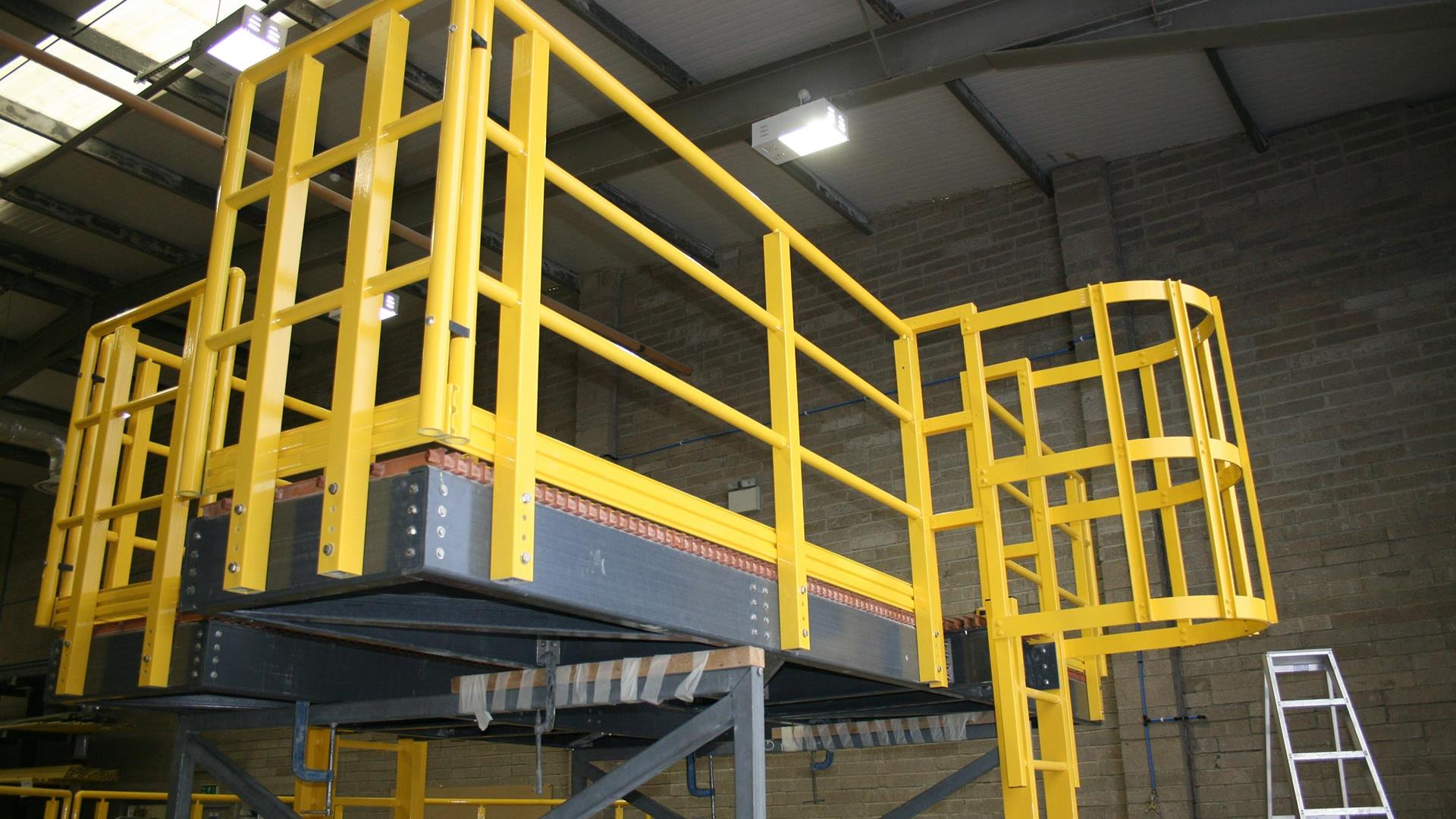 A platform with yellow fiberglass ladder and railings