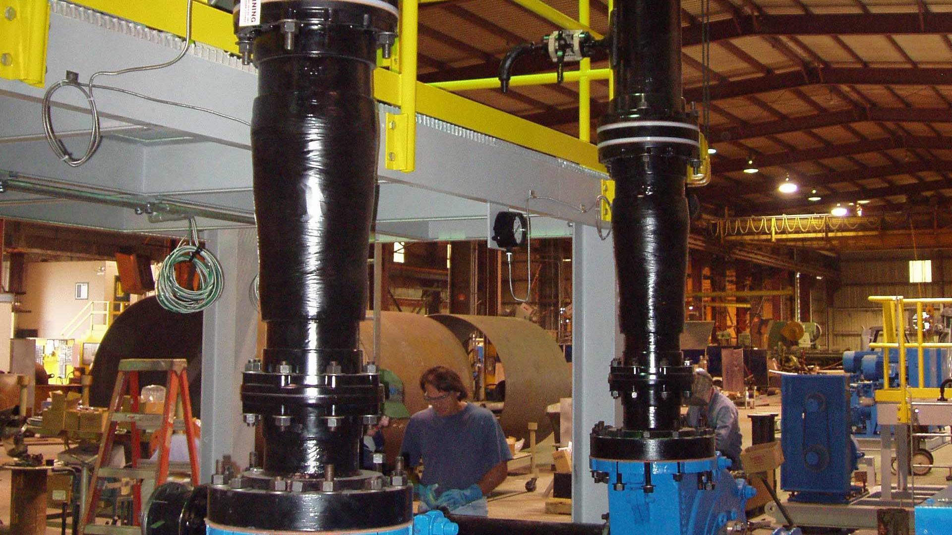 Two black Silver Streak Fiberglass Pipes in a manufacturing facility