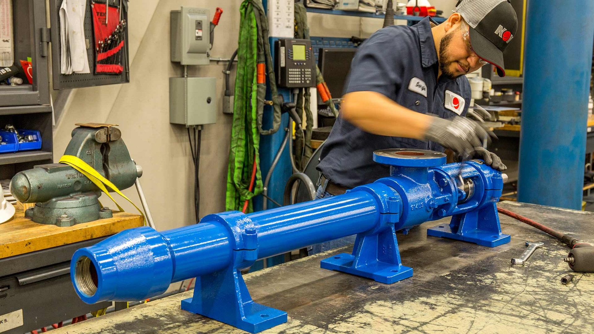 An NOV employee working on an L-Frame Pump in a workshop.