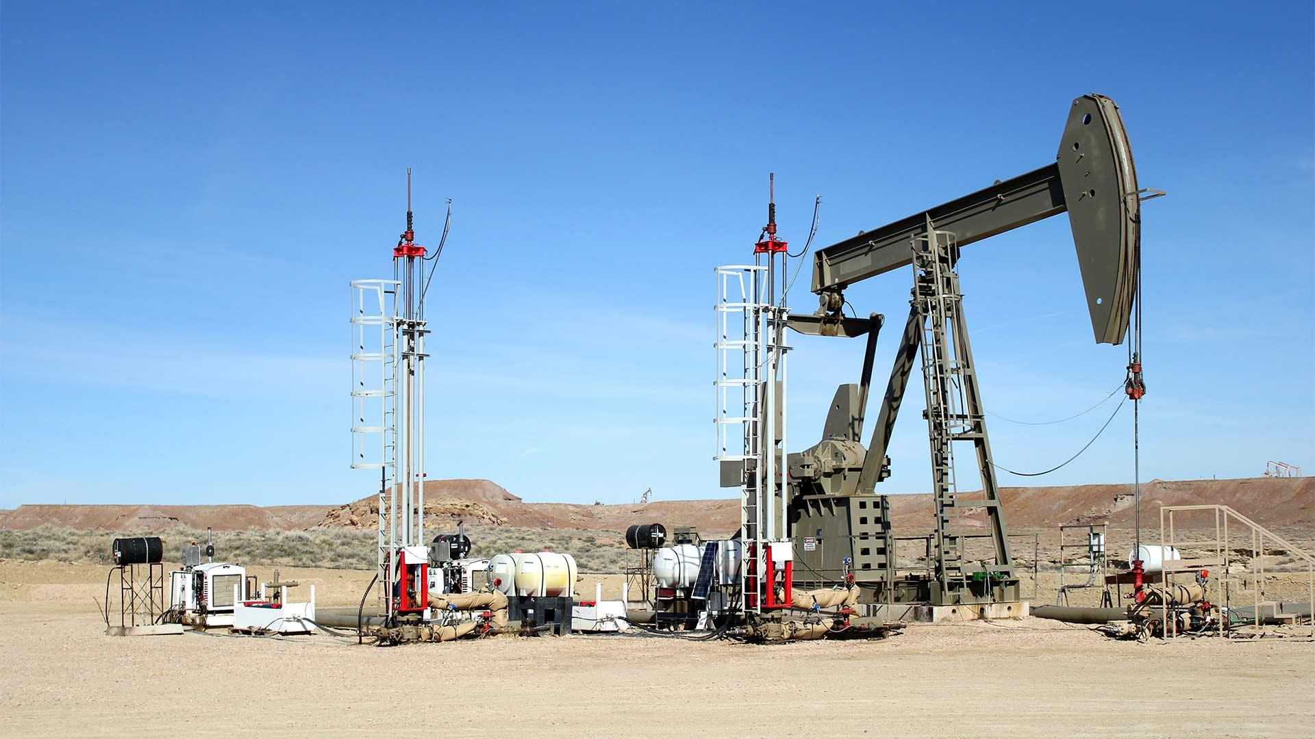 A pair of Morlift Hydraulic Rod Pumping Systems installed near a pump rig