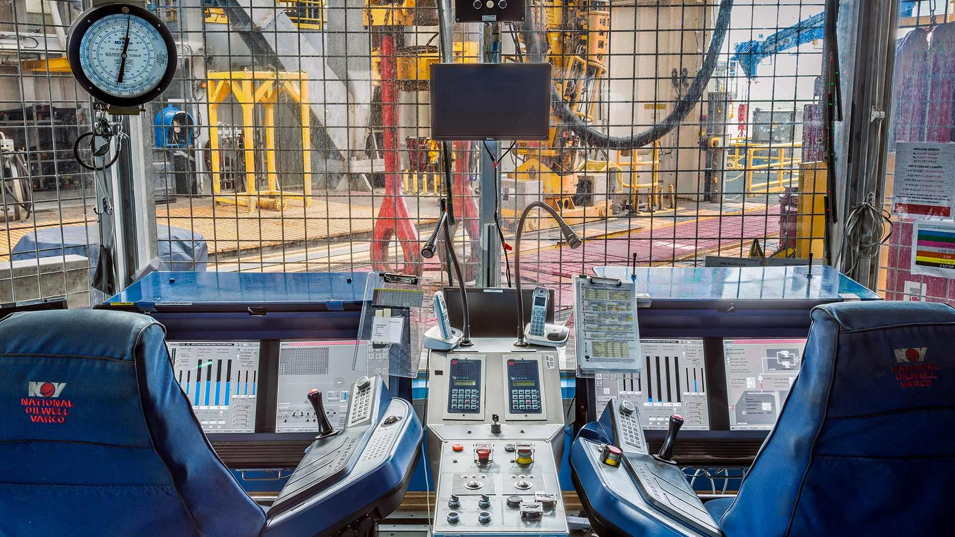 Two NOV Cyberbase drillers chairs and drilling monitor screens in drilling cabin on offshore platform