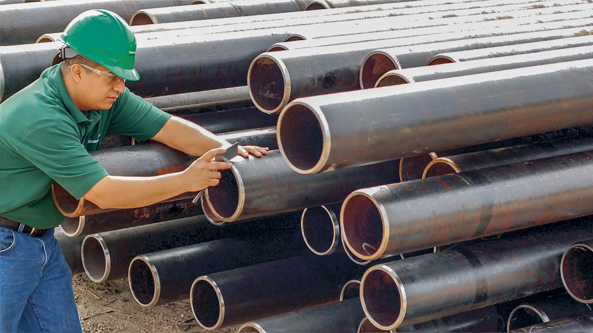 image of an NOV employee inspecting line pipe.