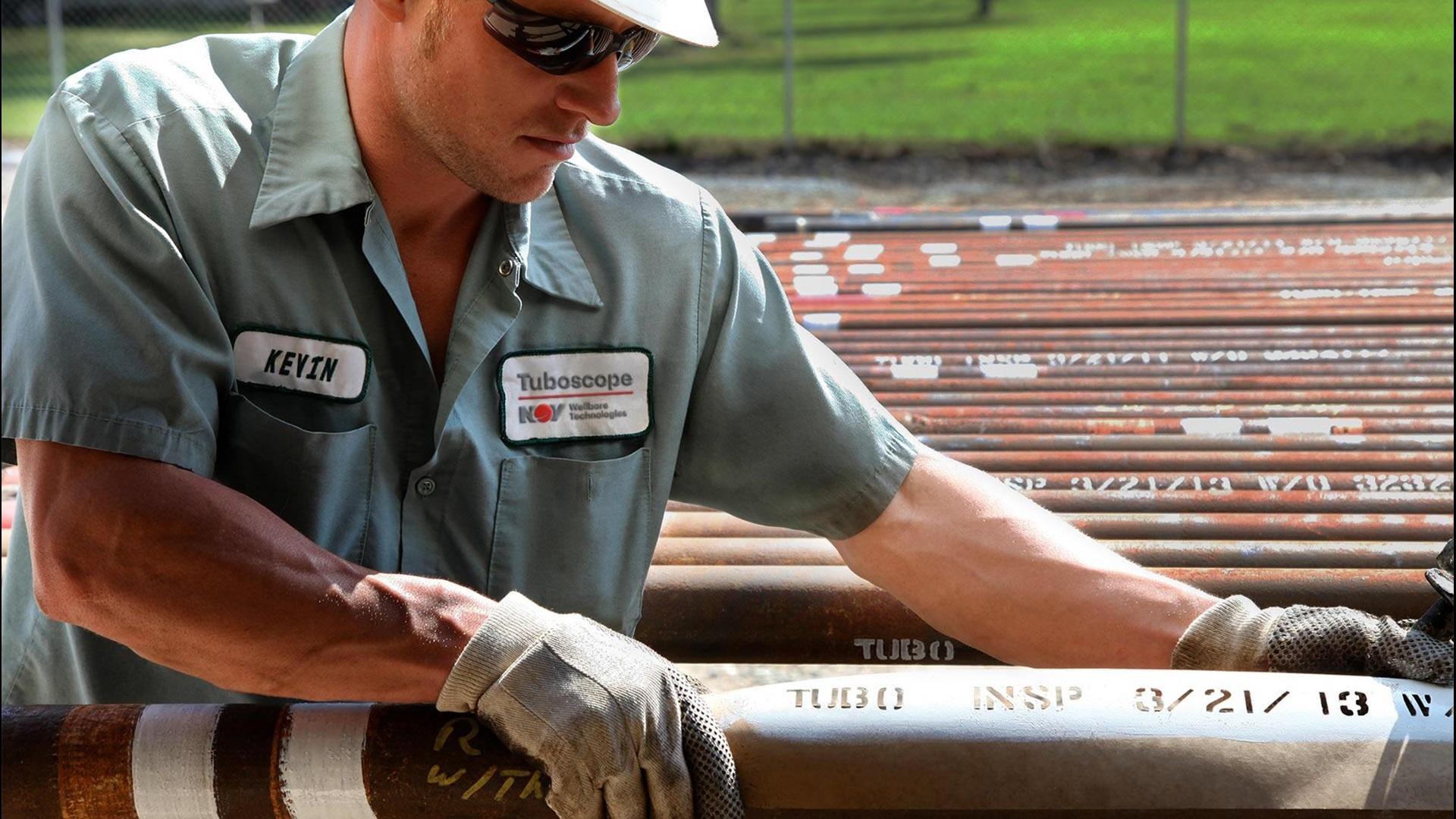 Image of an NOV employee applying a Tuboscope stencil to tubing.