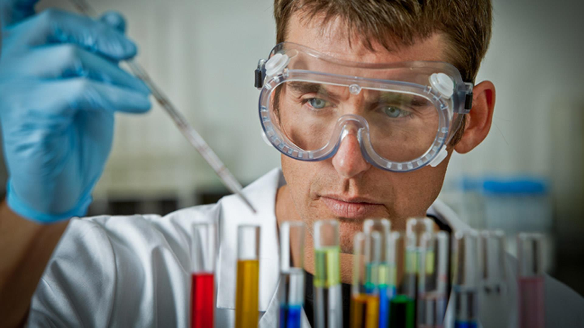 A technician examines a series of chemicals for the PETROS Fluid System