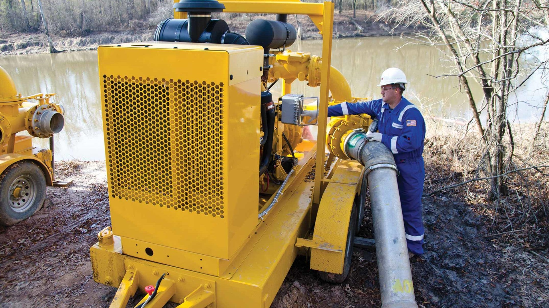 A technician manages water transfer equipment onsite