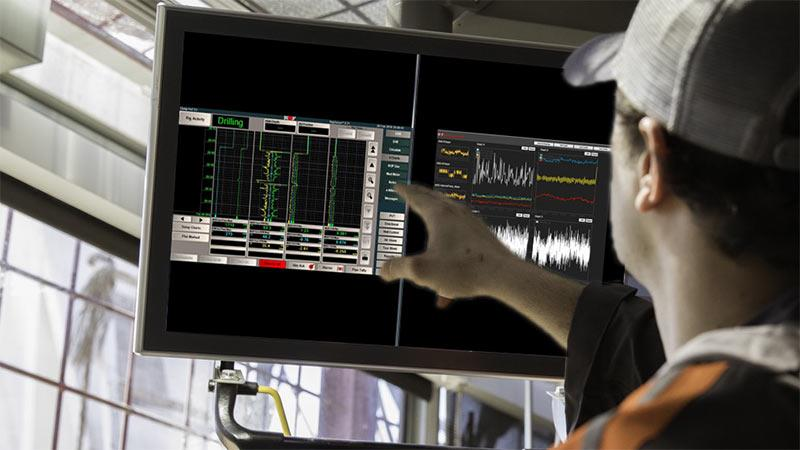 A technician points at a screen displaying software used for drilling