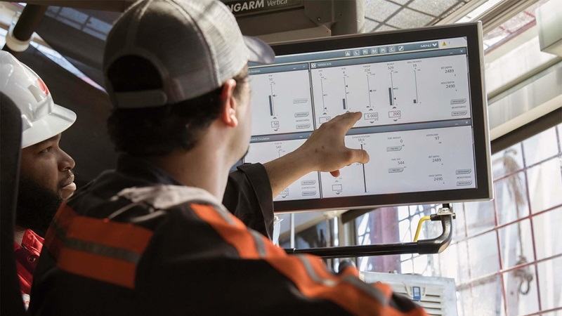 A rigger points to a screen running the NOVOS software system