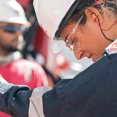 A rig technician in safety gear aligns a downhole tool