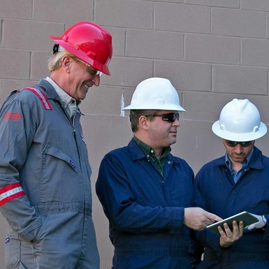 A group of technicians in safety gear discuss a booklet