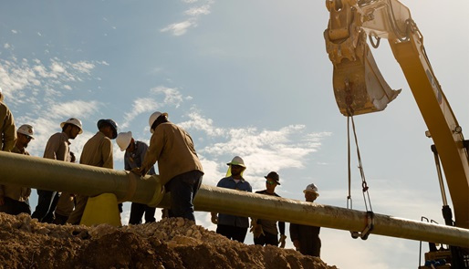 Work crew laying pipeline for Completion & Production Solutions