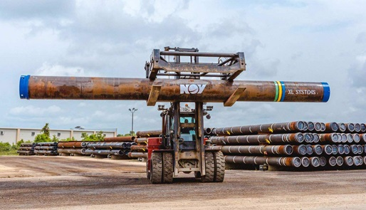 A forklift carries an XL Systems large diameter pipe through a storage yard