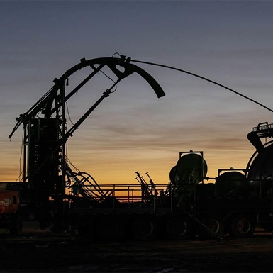 A tool used for completion and production silhouetted against a sunset