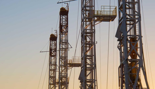 A series of rig towers silhouetted against the sky at dusk