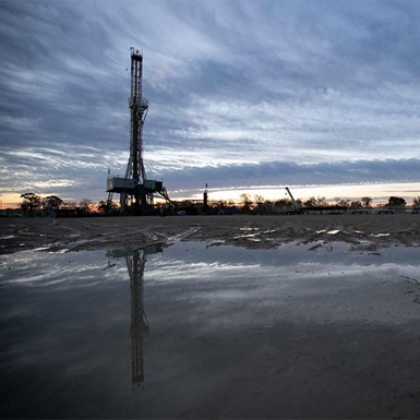 A rig in the distance is reflected in a puddle