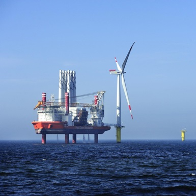 Offshore jackup rig with and wind turbine at sea