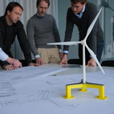 Engineering team reviewing wind turbine drawings