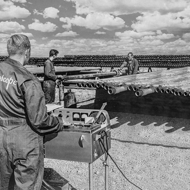 Vintage image of Tuboscope employees performing pipe inspections