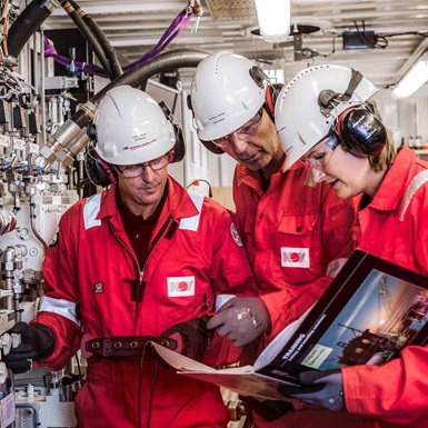A group of rig trainers reference a guide while observing rig equipment