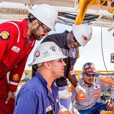 Four rig workers discuss tactics while examining a drill pipe connection on a rig