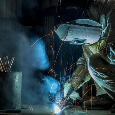 Welder fabricating equipment in warehouse
