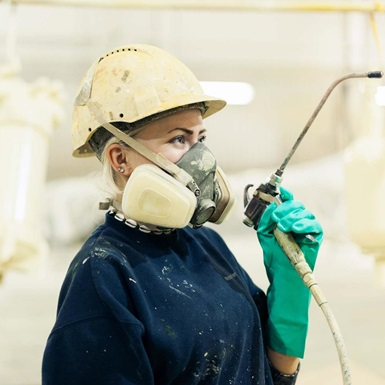 Technician with respirator mask sandblasting and/or painting