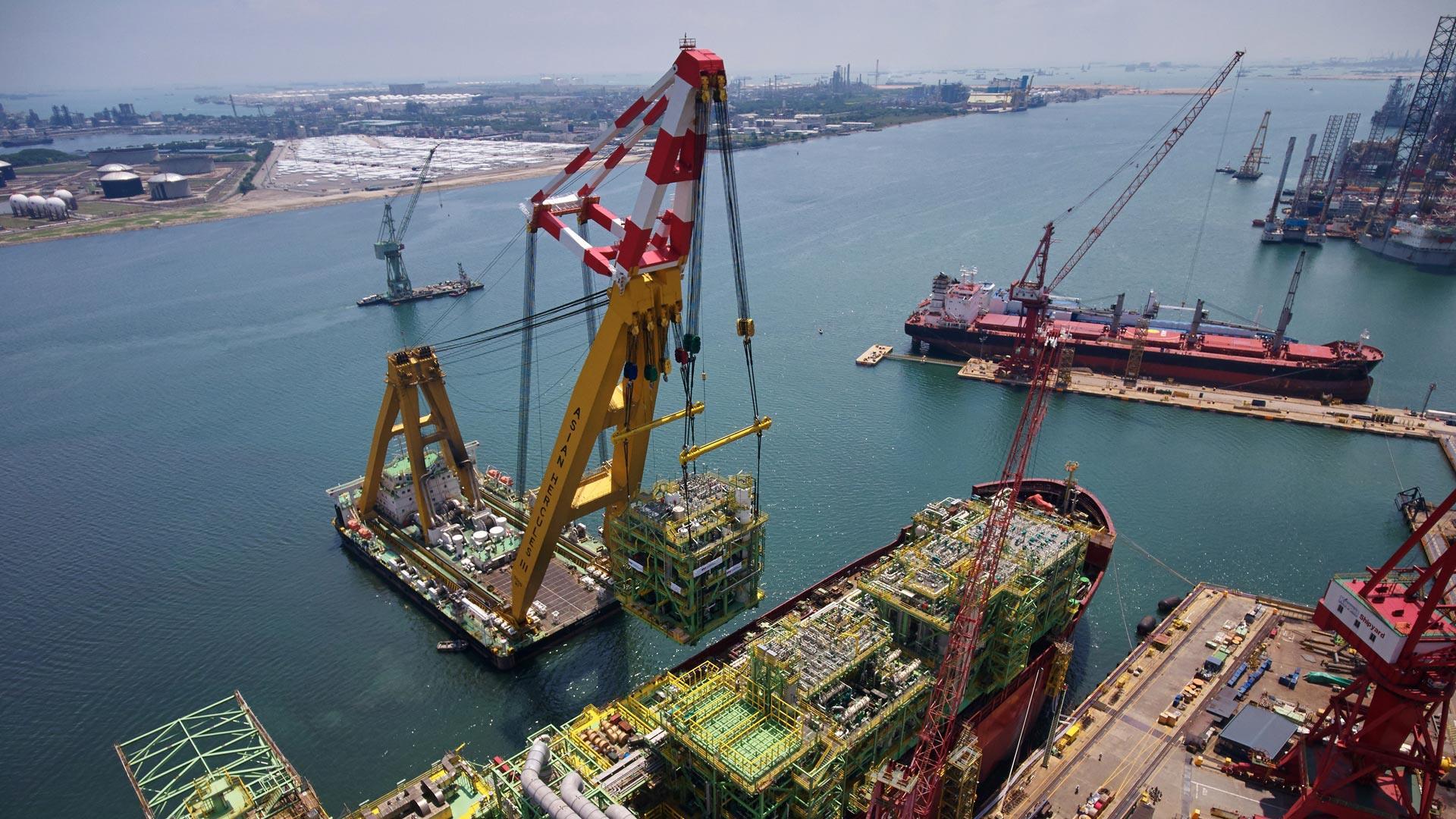 Crane lowering equipment onto ocean vessel