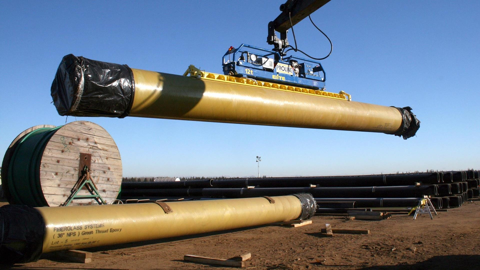 A crane moves a section of green thread fiberglass pipe