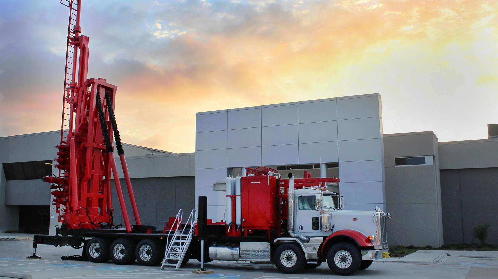 An erected Hydra Rig BOP Handler parked in front of a building