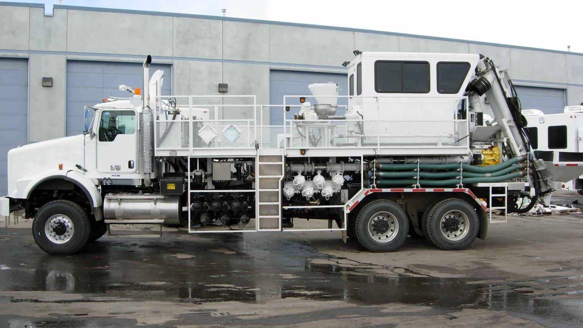 A side view of a parked white truck-mounted fracturing blender