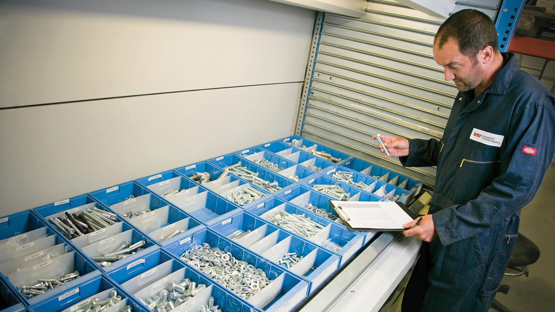 NOV technician reviewing bins of Wireline PCE Spares and Operational Accessories