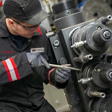 An Aftermarket services technician works on a piece of Wireline equipment