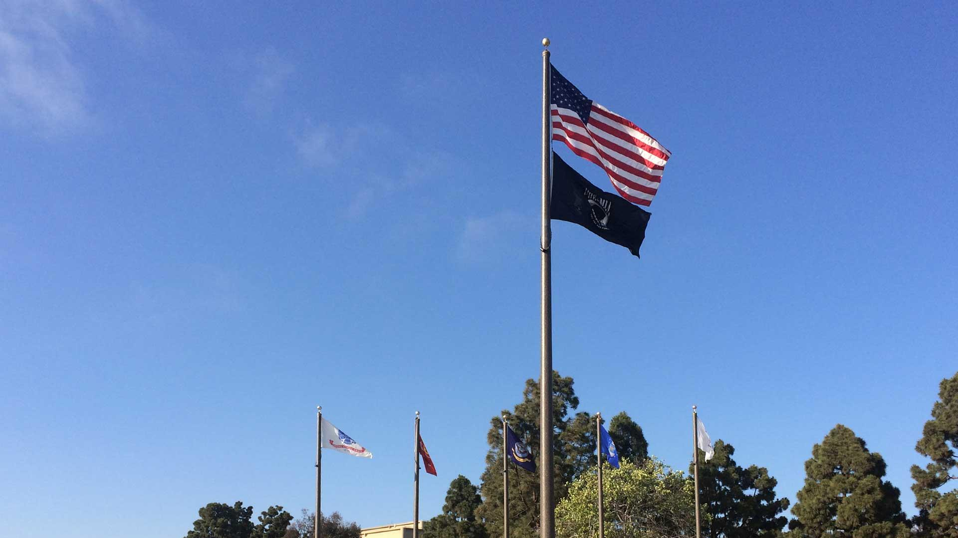 A series of Ameron flag poles displayed in front of a small monument.