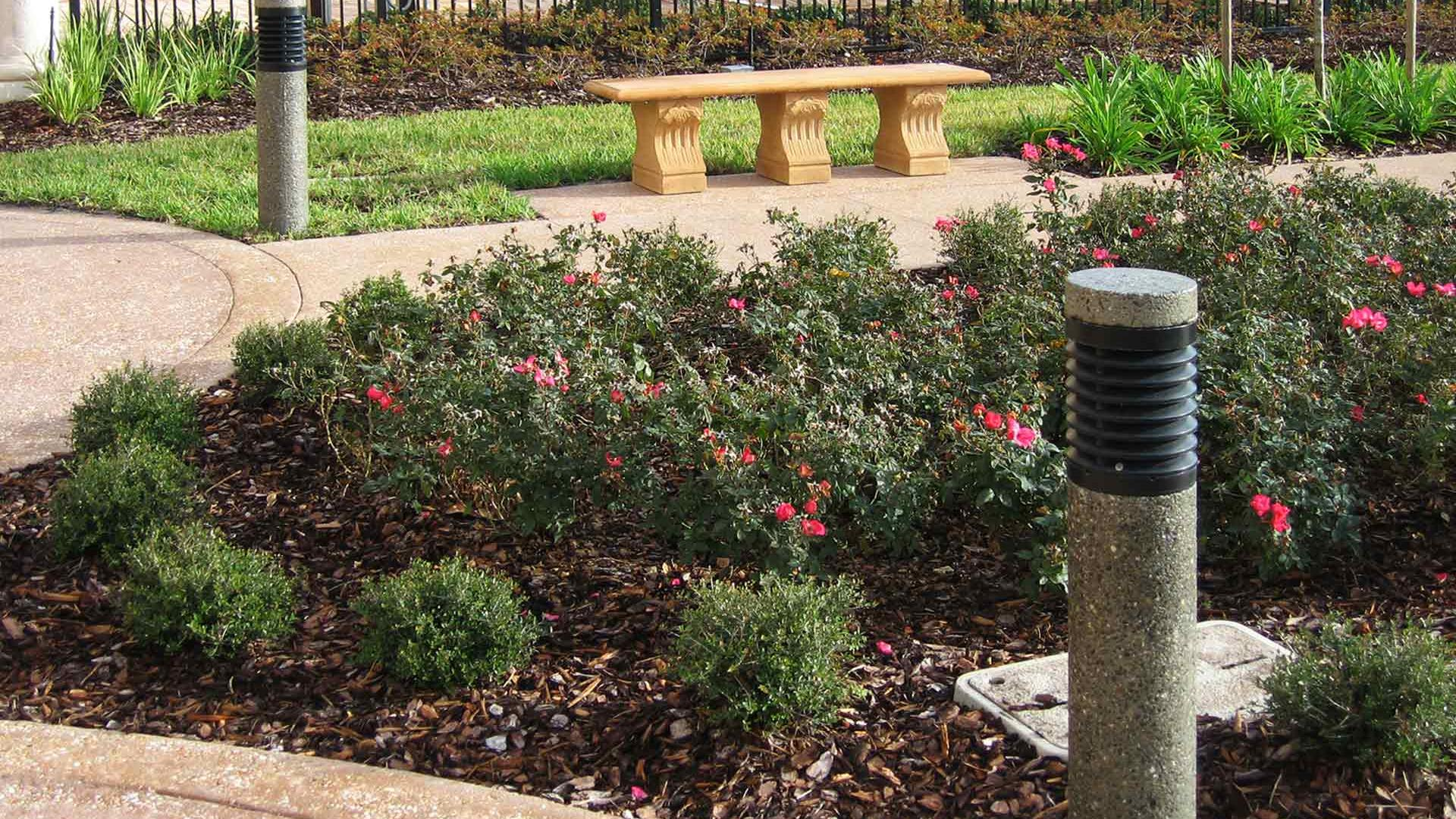 Two Ameron Round Louvered Bollards featured along a path