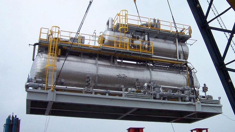 Crude oil treatment module being lifted by crane as it prepares for deployment