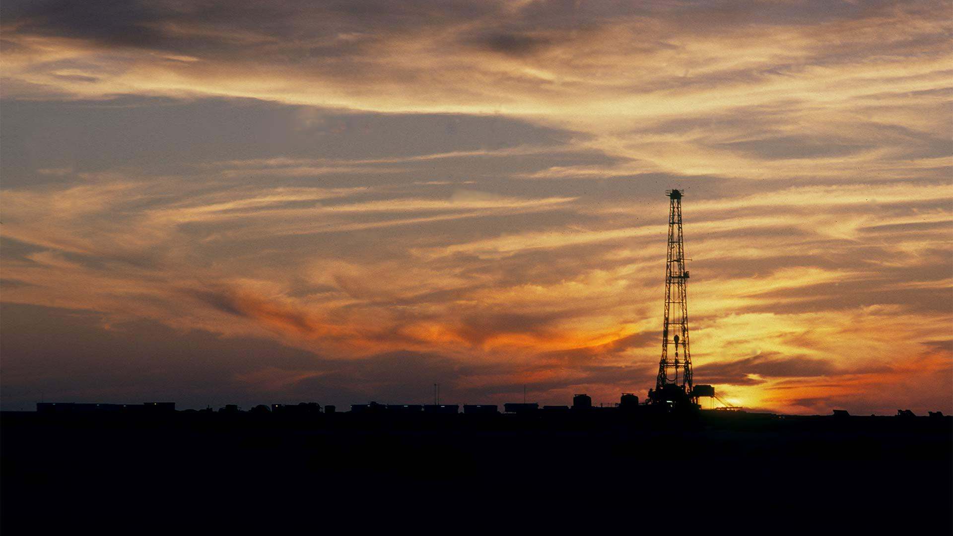 A rig silhouetted against a sunset