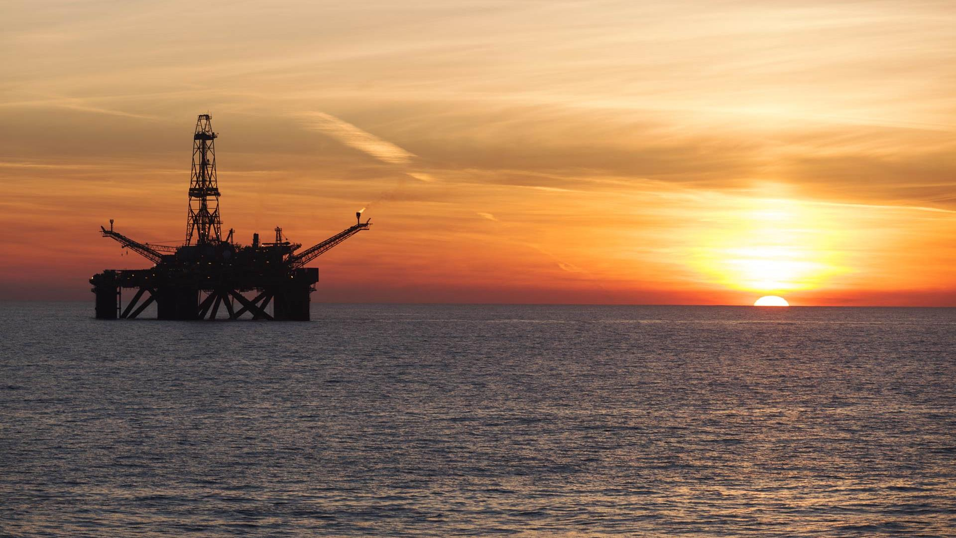 sun setting on offshore rig under construction