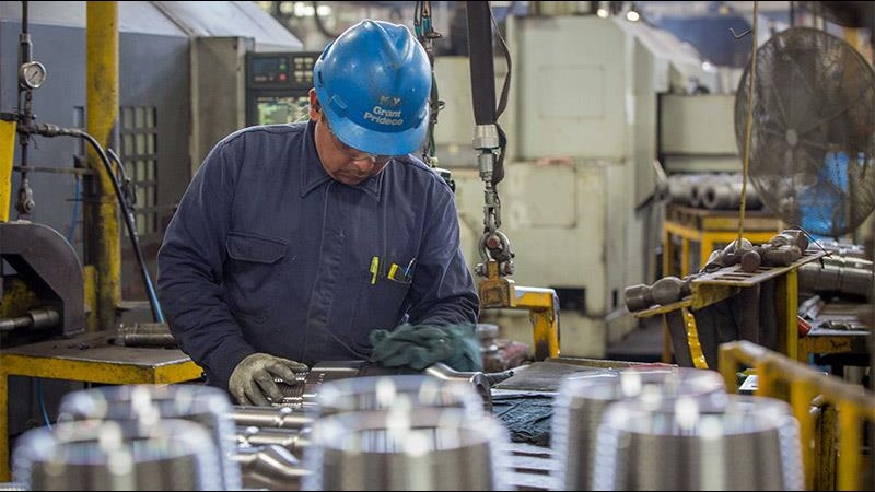 A Grant Prideco technician inspects a pallet of connectors during manufacturing
