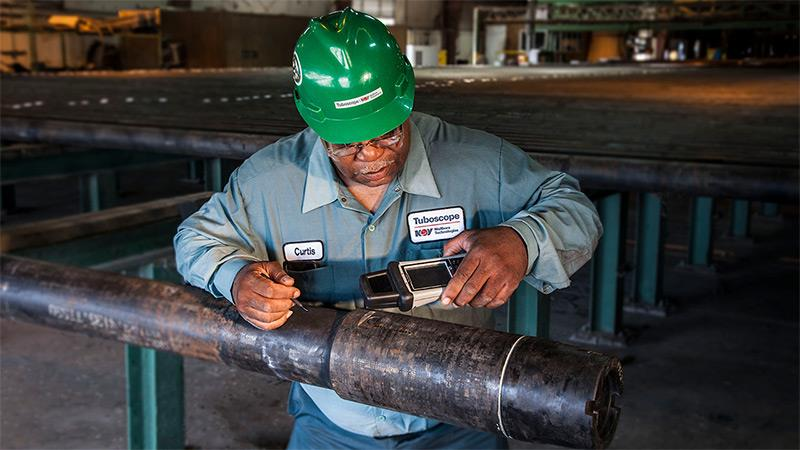 An NOV Tuboscope inspector inspects a pipe fitted with TracID