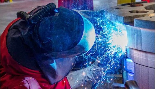 Person welding equipment in an industrial setting